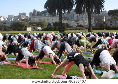 Big yoga group exercising on public ground