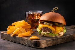 Big yummy burger with cheese, fries and a glass of cola on a wooden board on a black background, angle view. Fast food set.