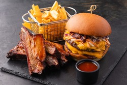 Big yummy burger with double cutlet, fries and fried ribs with barbecue sauce on a black slate background. Fast food set or hamburger menu, angle view.