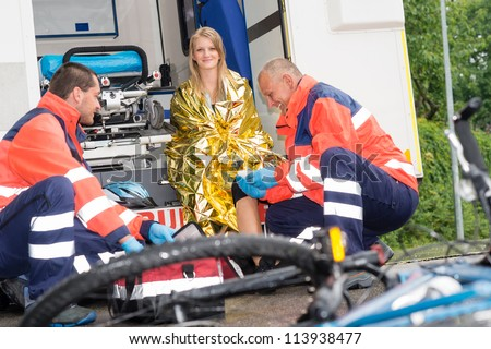 Bike accident woman emergency doctor bandage leg in ambulance smiling