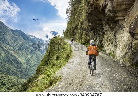 "Bike adventure travel photo. Bike tourists  ride on the ""road of death""  downhill track  in Bolivia. In the background sky circles a condor over the scene. #340984787"
