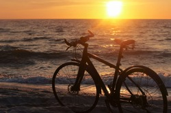 Bike and sunset by the sea. Black bike by the sea.