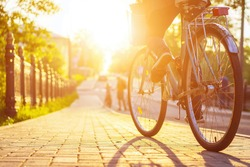 Bike at the summer sunset on the tiled road in the city park. Cycle closeup wheel on blurred summer background. Cycling down the street to work at summer sunset. Bicycle and ecology lifestyle concept.