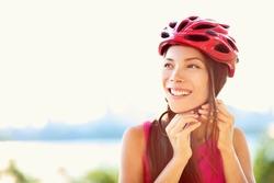 Bike helmet - woman putting biking helmet on outside during bicycle ride.
