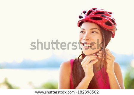 Bike helmet - woman putting biking helmet on outside during bicycle ride.
