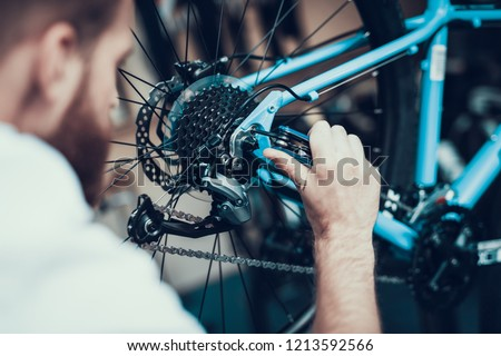 Bike Mechanic Repairs Bicycle in Workshop. Closeup Portrait of Young Blurred Man Examines and Fixes Modern Cycle Transmission System. Bike Maintenance and Sport Shop Concept #1213592566