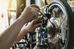 Bike mechanic repairs folding bicycle in Workshop. adjust Rear Derailleur ,cassette sprocket . Bicycle Maintenance and Repair concept