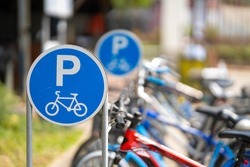 Bike parking sign with a blurred bicycle background.