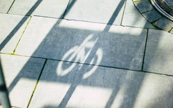 Bike parking stand shadow. A close up photo of a bike parking stand shadow on the street tile.