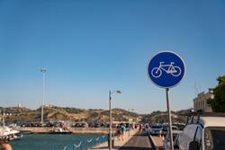 Bike path area and blue bike sign in pedestrian area near the bay