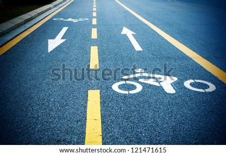Bike path, dark road and yellow lines.