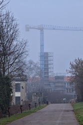 Bike path with buildings and a crane in the distance on a foggy day in an italian town in winter