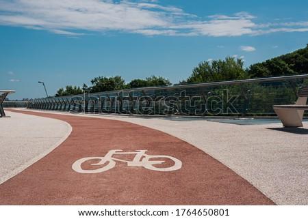 Bike path with of bicycle symbol. Pink bike lane with non-slip acrylic coating on city footbridge stock photo