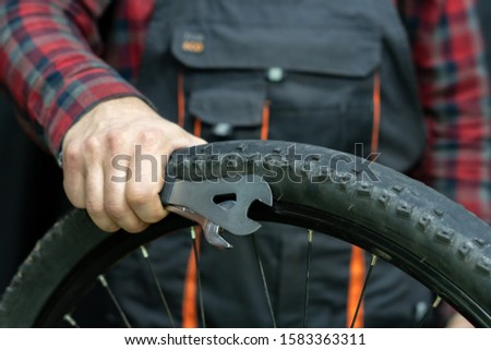 bike repair. Bike mechanic in the workshop. A mechanic holds tools and a bicycle wheel in his hand. Hands of the master and keys close-up. A man in a fashionable plaid shirt and work overalls.