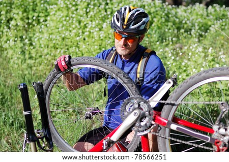 Bike repair. Young man repairing mountain bike in the forest - stock photo