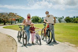 bike ride. family walks in the park on a sunny day. there are seven face masks of different colors on the faces, against the coronavirus covid-19