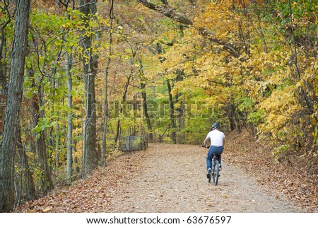 bike rider on trail in autumn woods