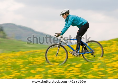 Bike riding - woman downhill on bike in dandelion meadow (intentional motion blur)