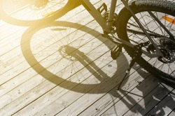bike shadow on old wood texture, front and background blurred with bokeh effect