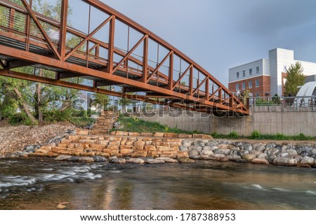 bike trail and footbridge - Cache la Poudre River at whitewater park in downtown of Fort Collins Colorado with Powerhouse Energy Campus of Colorado State University in background Photo stock ©