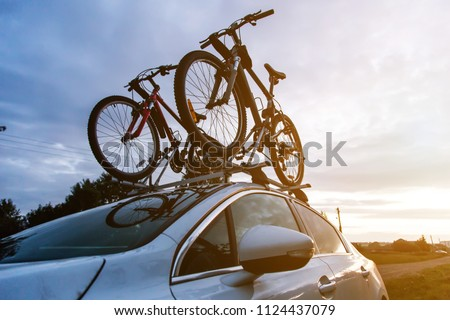 Bike transportation - two bikes on the roof of a car against a beautiful sky. the end of the transportation of large loads and travel by car stock photo