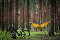 Bike trip to the forest. Bicycle and green military backpack in the focus, man relaxing in the hammock hanging among the red pine trees in the background. Selective focus. Travel. Bike packing concept