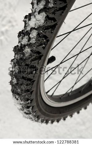 bike wheel tire on snow, extreme sports concept - stock photo