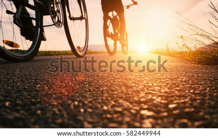Photo of Bike wheels close up image on asphalt sunset road