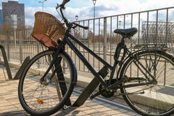 Bike with a grocery basket is parked in an equipped bicycle parking. Riding and cycling in the city. Shopping for groceries and home delivery by bike.