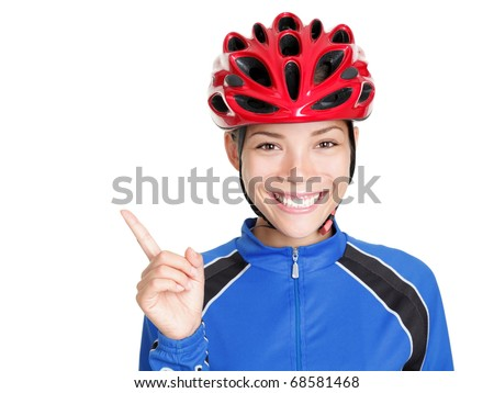 Bike woman wearing bicycle helmet pointing at copy space isolated on white background. Beautiful young asian chinese / white caucasian woman in biking outfit and red biking helmet