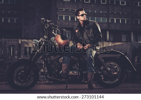 Biker and his bobber style motorcycle on a city streets  #273101144