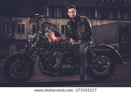 Biker and his bobber style motorcycle on a city streets  #273103217