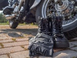 Biker boots and fingerless leather gloves with laces close-up standing near the wheel of a motorcycle chopper