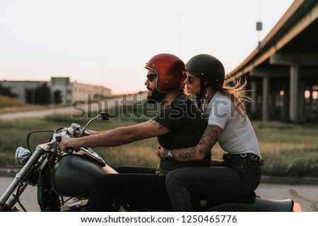 Biker couple riding down the road in the sunset