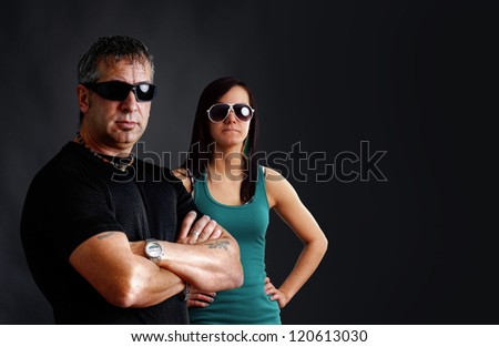 Biker couple: tough guy with tattoos and black sunglasses, arms crossed, looking at camera with pretty young brunette woman, studio shot over black.