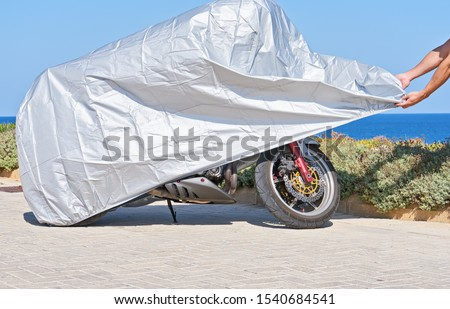 Biker covers motorcycle with waterproof cover with silver reflective surface protective. Motorbike covered with fabric shield parked at outdoor