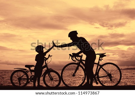 Biker family silhouette daddy and son at the beach at sunset