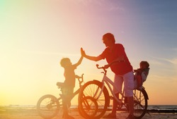 Biker family silhouette, father with two kids on bikes