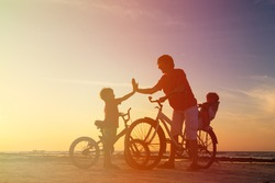 Biker family silhouette, father with two kids on bikes at sunset