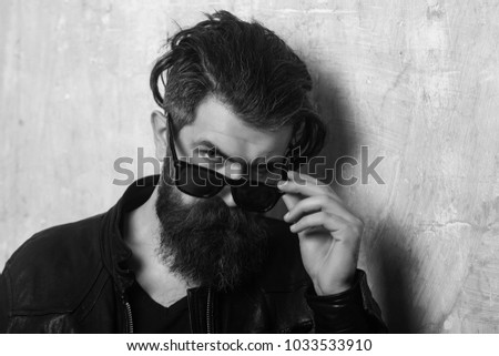 Biker fashion and beauty. Fashion model on textured wall background. Guy with serious face. Man with long beard and mustache. Hipster in leather jacket and glasses. #1033533910