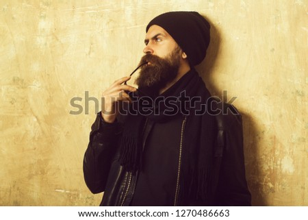 Biker fashion and beauty. Fashion model on textured wall background. Guy with serious face. Man with long beard and mustache. Hipster in leather jacket and hat with glasses. #1270486663