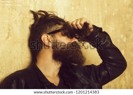 Biker fashion and beauty. Fashion model on textured wall background. Man with long beard and mustache. Hipster in leather jacket and glasses. Guy with serious face. #1201214383
