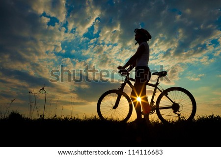 Biker-girl at the sunset on the meadow #114116683