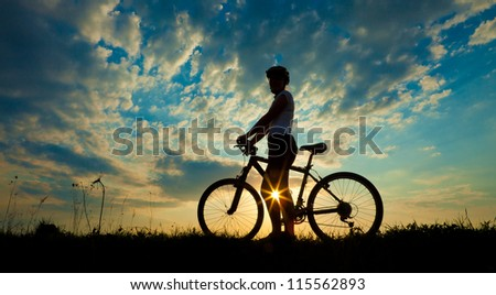Biker-girl at the sunset on the meadow #115562893