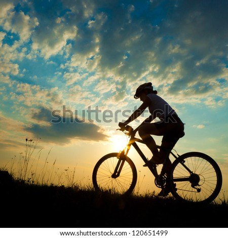 Biker-girl at the sunset on the meadow #120651499