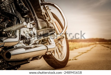 Biker girl riding on a motorcycle. Bottom view of the legs in leather boots. #248941618