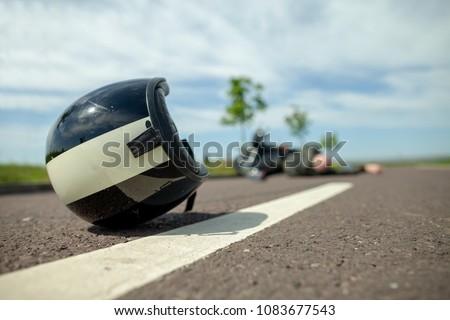 biker helmet lies on street near a motorcycle accident #1083677543