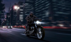 biker in black leather fast riding chopper motorcycle while being chased by car downtown at night