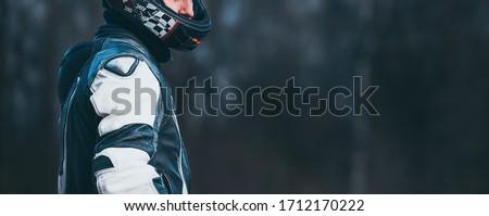 Photo of  Biker in protective suit with a helmet.