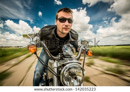 Biker in sunglasses and leather jacket racing on the road